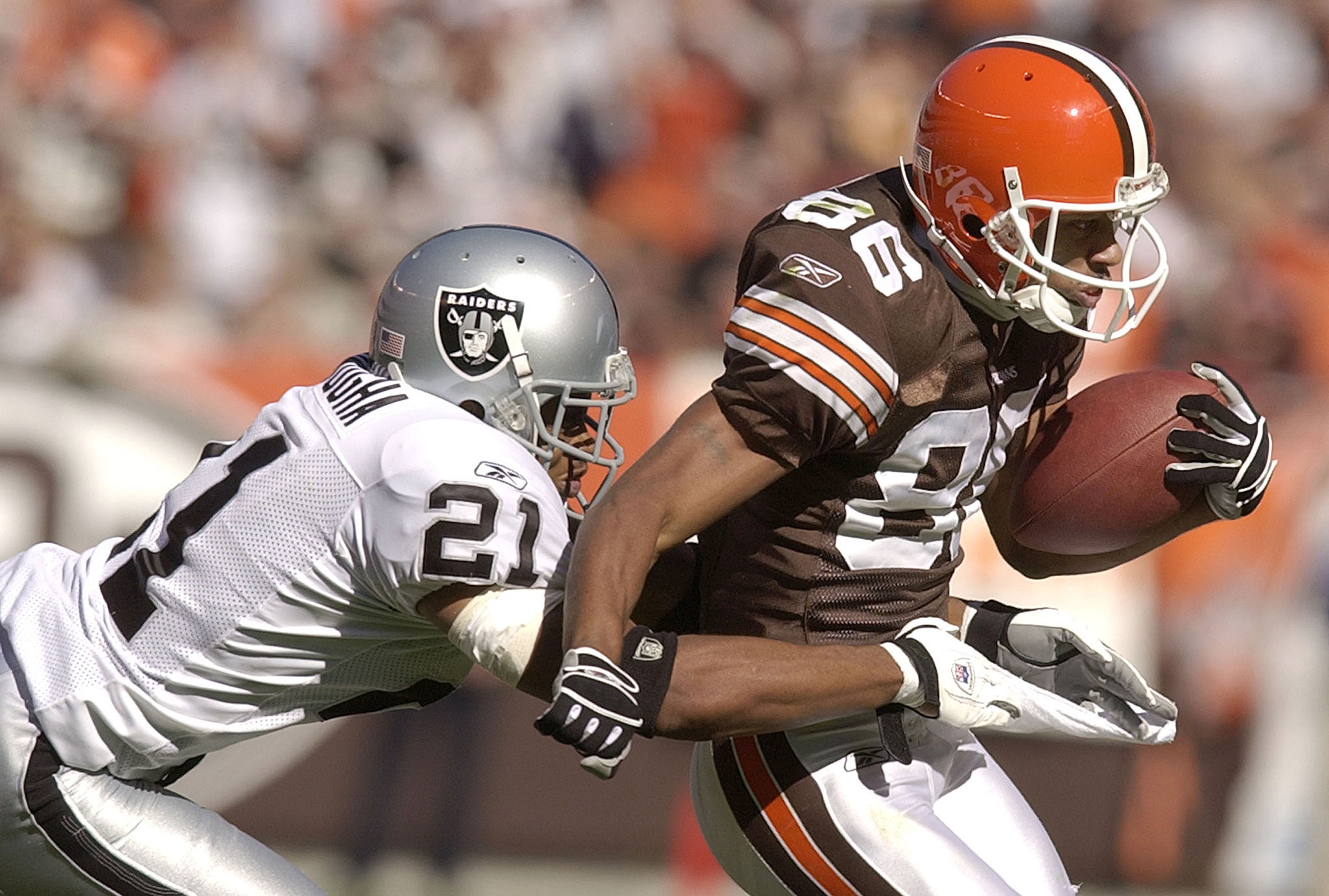 CLEVELAND, OH - OCTOBER 12:  Wide receiver Dennis Northcutt #86 of the Cleveland Browns is tackled by Nnamdi Asomugha of the Oakland Raiders during the third quarter on October 12, 2003 at Cleveland Browns Stadium in Cleveland, Ohio. The Browns defeated t