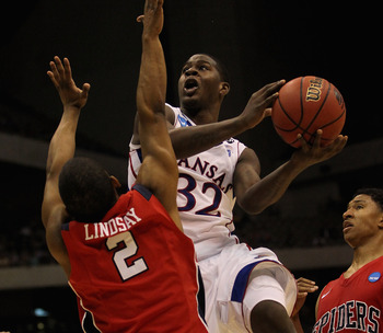 SAN ANTONIO, TX - MARCH 25:  Josh Selby #32 of the Kansas Jayhawks goes to the basket against Cedrick Lindsay #2 of the Richmond Spiders during the southwest regional of the 2011 NCAA men's basketball tournament at the Alamodome on March 25, 2011 in San A