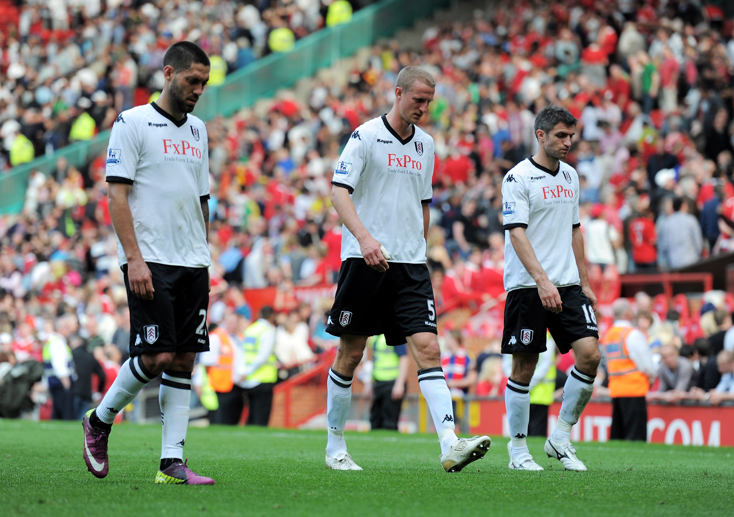 MANCHESTER, ENGLAND - APRIL 09: Brede Hangeland (C) of Fulham walks off dejected with Clint Dempsey (L) and Aaron Hughes after the Barclays Premier League match between Manchester United and Fulham at Old Trafford on April 9, 2011 in Manchester, England.