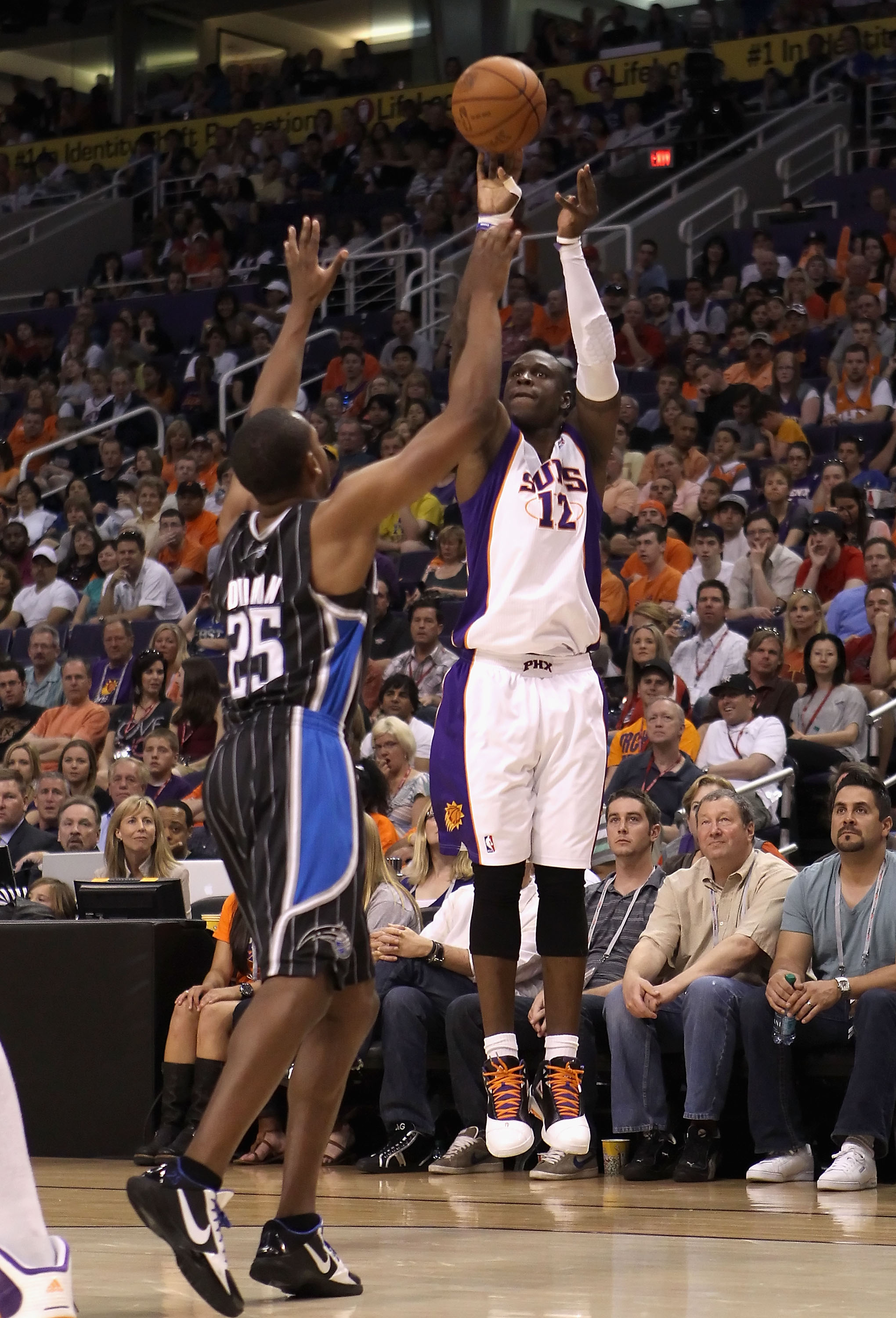 PHOENIX, AZ - MARCH 13:  Mickael Pietrus #12 of the Phoenix Suns attempts a three point shot over Chris Duhon #25 of the Orlando Magic during the NBA game at US Airways Center on March 13, 2011 in Phoenix, Arizona. The Magic defeated the Suns 111-88. NOTE