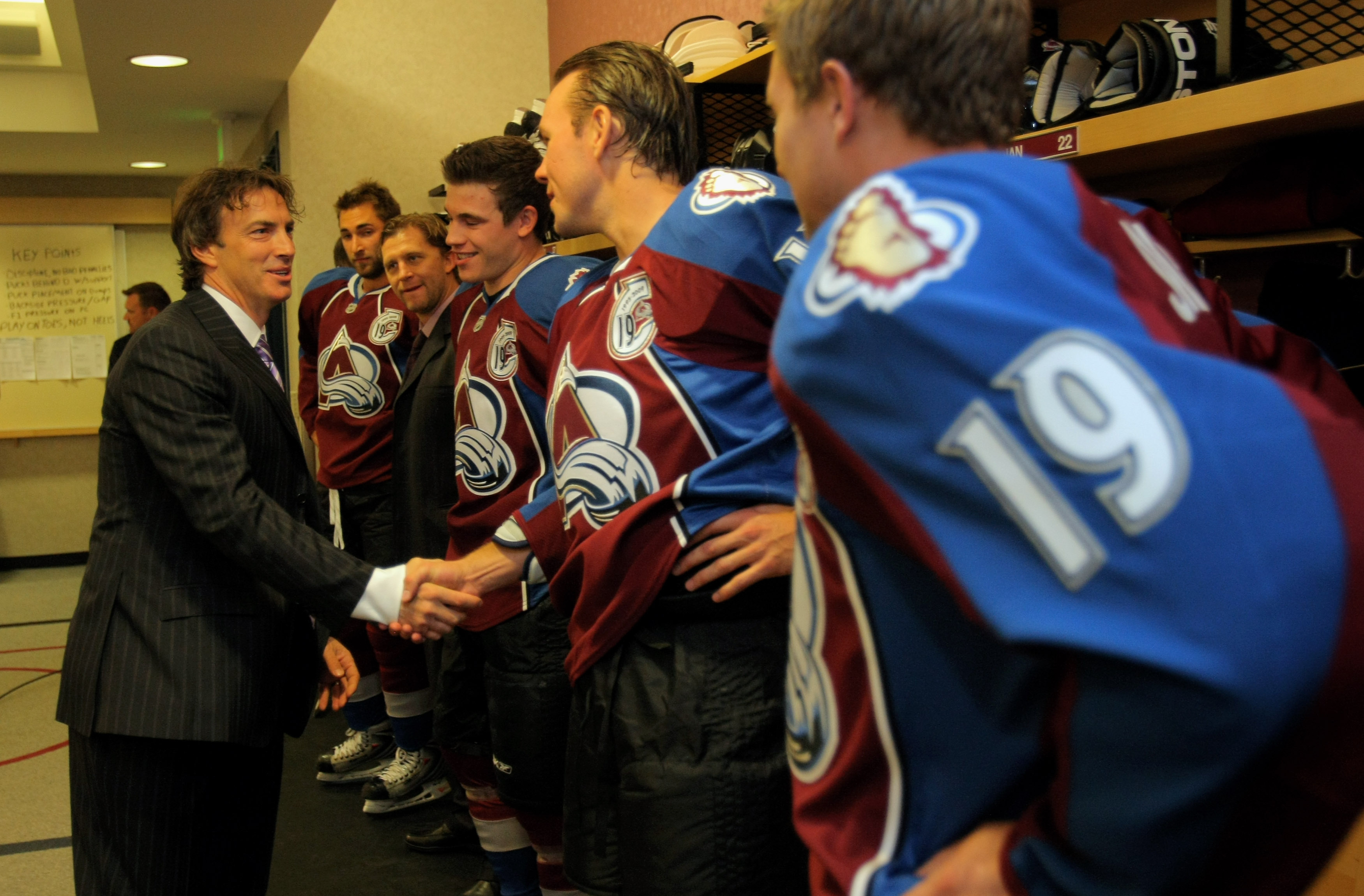 DENVER - OCTOBER 01:  Joe Sakic shakes the hand of Scott Hannan as he greets all the players of the Colorado Avalanche in the locker room on the night when Sakic's jersey was retired at the Pepsi Center on October 1, 2009 in Denver, Colorado.  (Photo by D