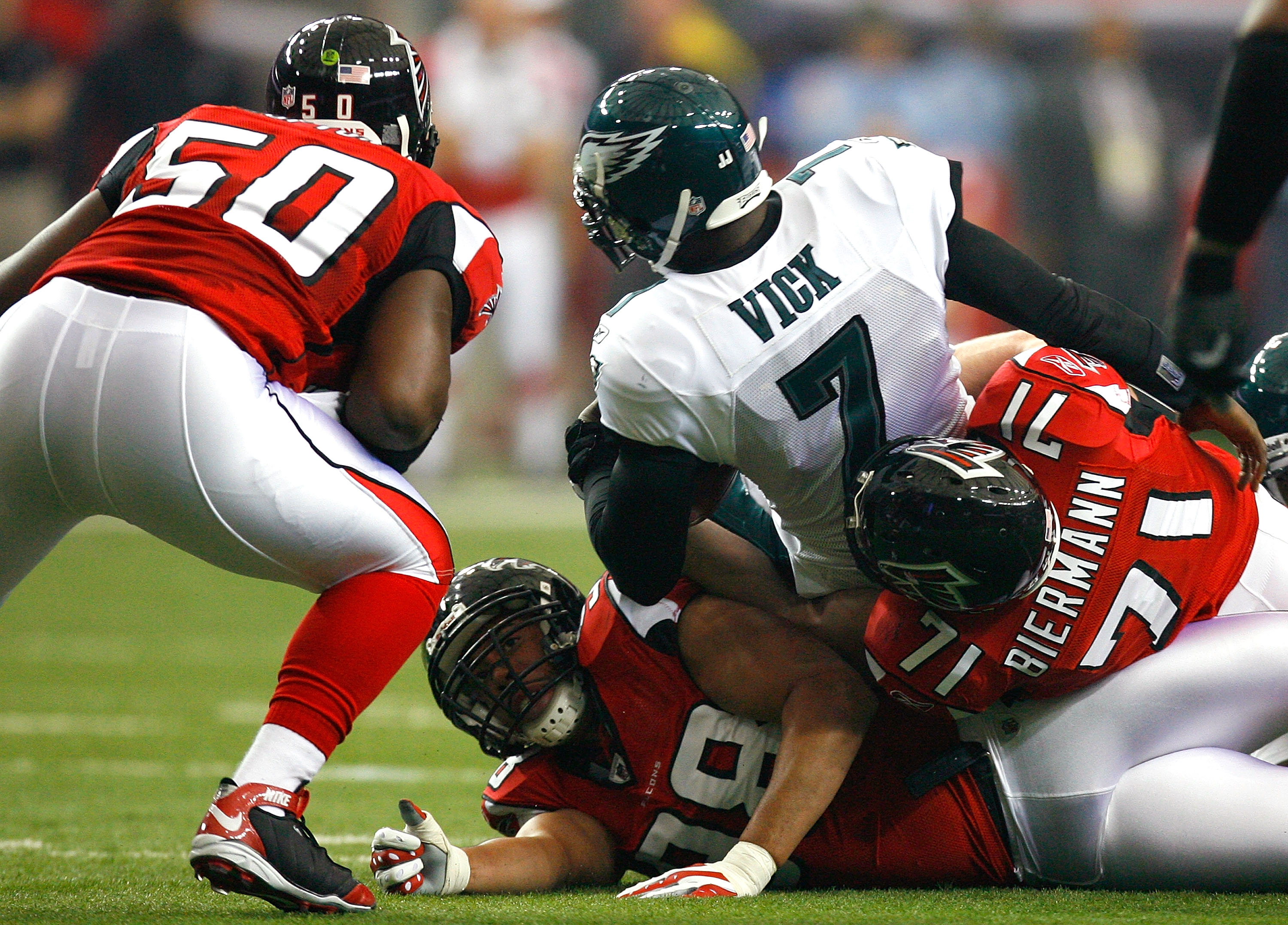 ATLANTA - DECEMBER 06:  Michael Vick #7 of the Philadelphia Eagles is tackled by Kroy Biermann #71, Curtis Lofton #50 and Jamaal Anderson #98 of the Atlanta Falcons at Georgia Dome on December 6, 2009 in Atlanta, Georgia.  (Photo by Kevin C. Cox/Getty Ima