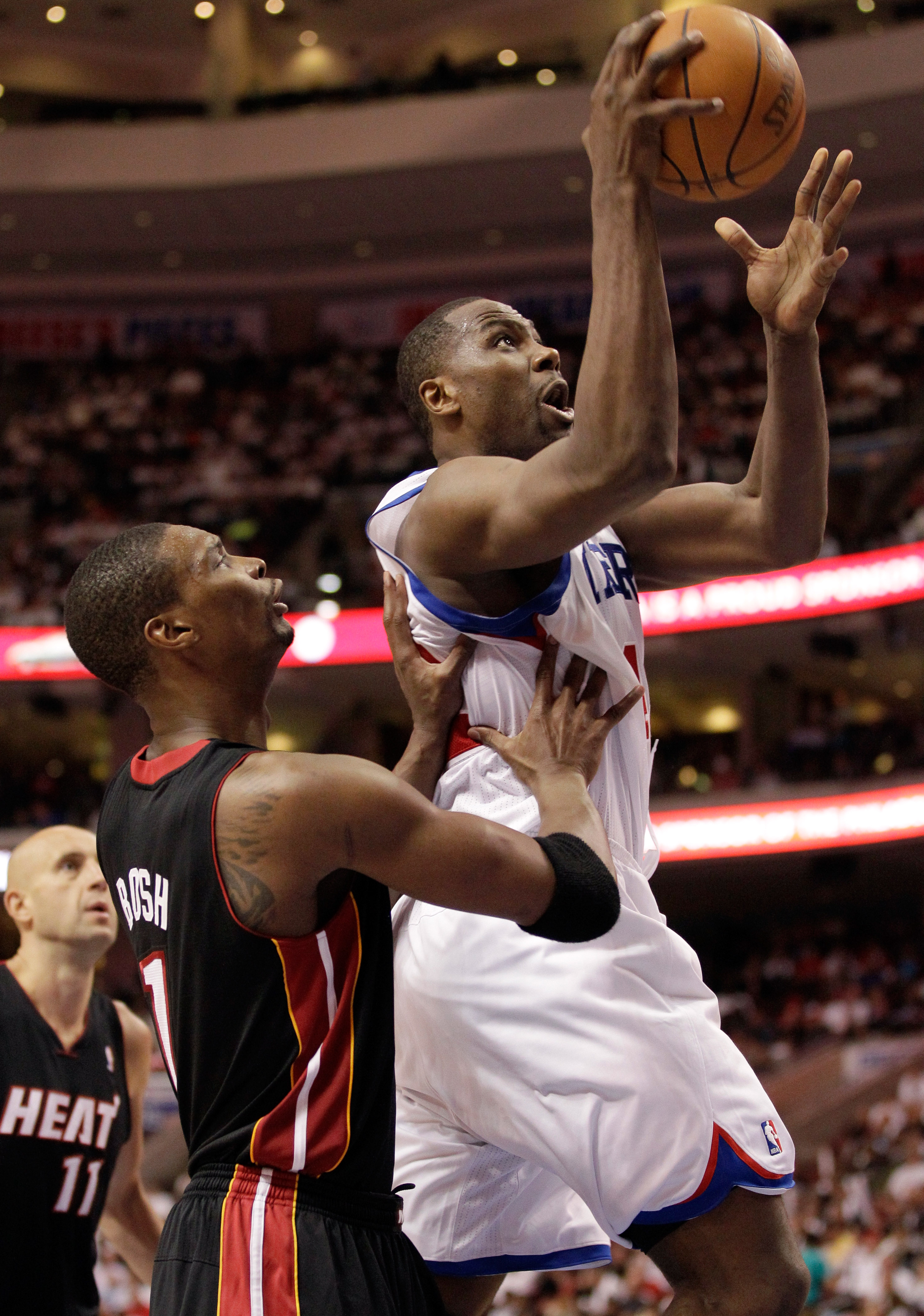 PHILADELPHIA, PA - APRIL 21: Elton Brand #42 of the Philadelphia 76ers (R) puts the ball up in front of Chris Bosh #1 of the Miami Heat during the second half of game three of the Eastern Conference Quarterfinals at Wells Fargo Center on April 21, 2011 in