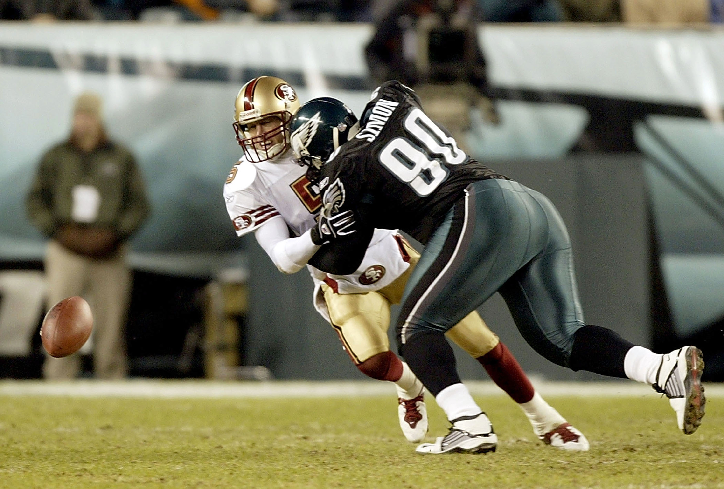PHILADELPHIA - DECEMBER 21:  Quarterback Jeff Garcia #5 of the San Francisco 49ers fumbles the ball after being hit by Corey Simon #90 of the Philadelphia Eagles on December 21, 2003 at Lincoln Financial Field in Philadelphia, Pennsylvania.  (Photo by Ezr