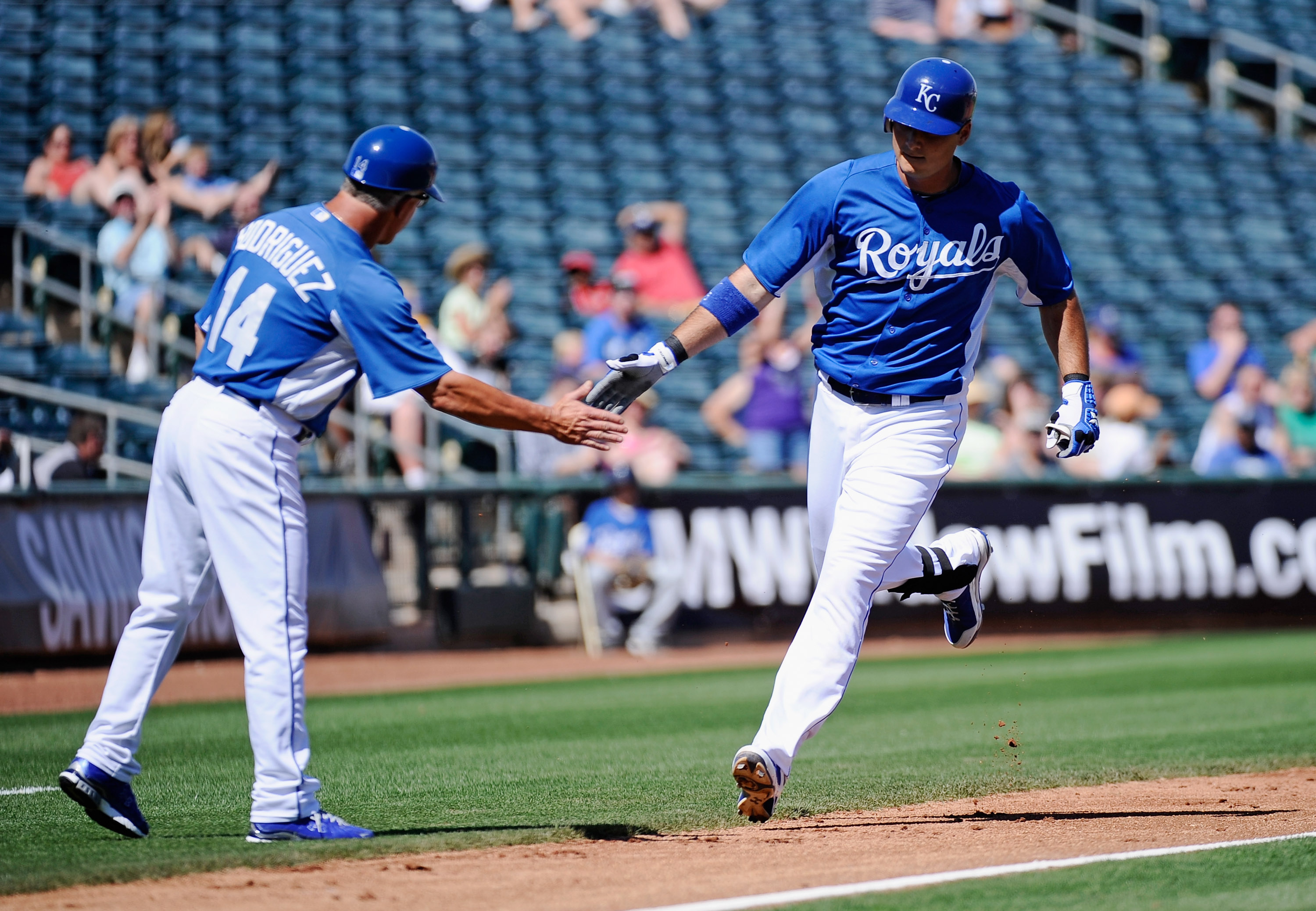 SURPRISE, AZ - MARCH 12:  Clint Robinson #25 of the Kansas City Royals is congratulated by the thrid base coach Eddie Rodriguez #14 aftet hitting a one run home run during the first inning of the spring training baseball game against the Los Angeles Dodge