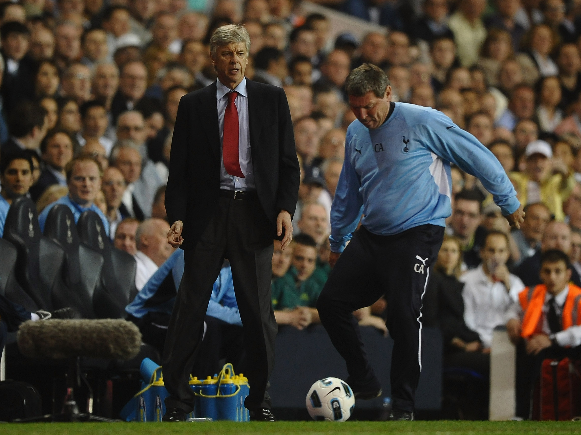 LONDON, ENGLAND - APRIL 20:  Spurs coach, Clive Allen kicks the match ball as Arsenal manager Arsene Wenger looks on during the Barclays Premier League match between Tottenham Hotspur and Arsenal at White Hart Lane on April 20, 2011 in London, England.  (