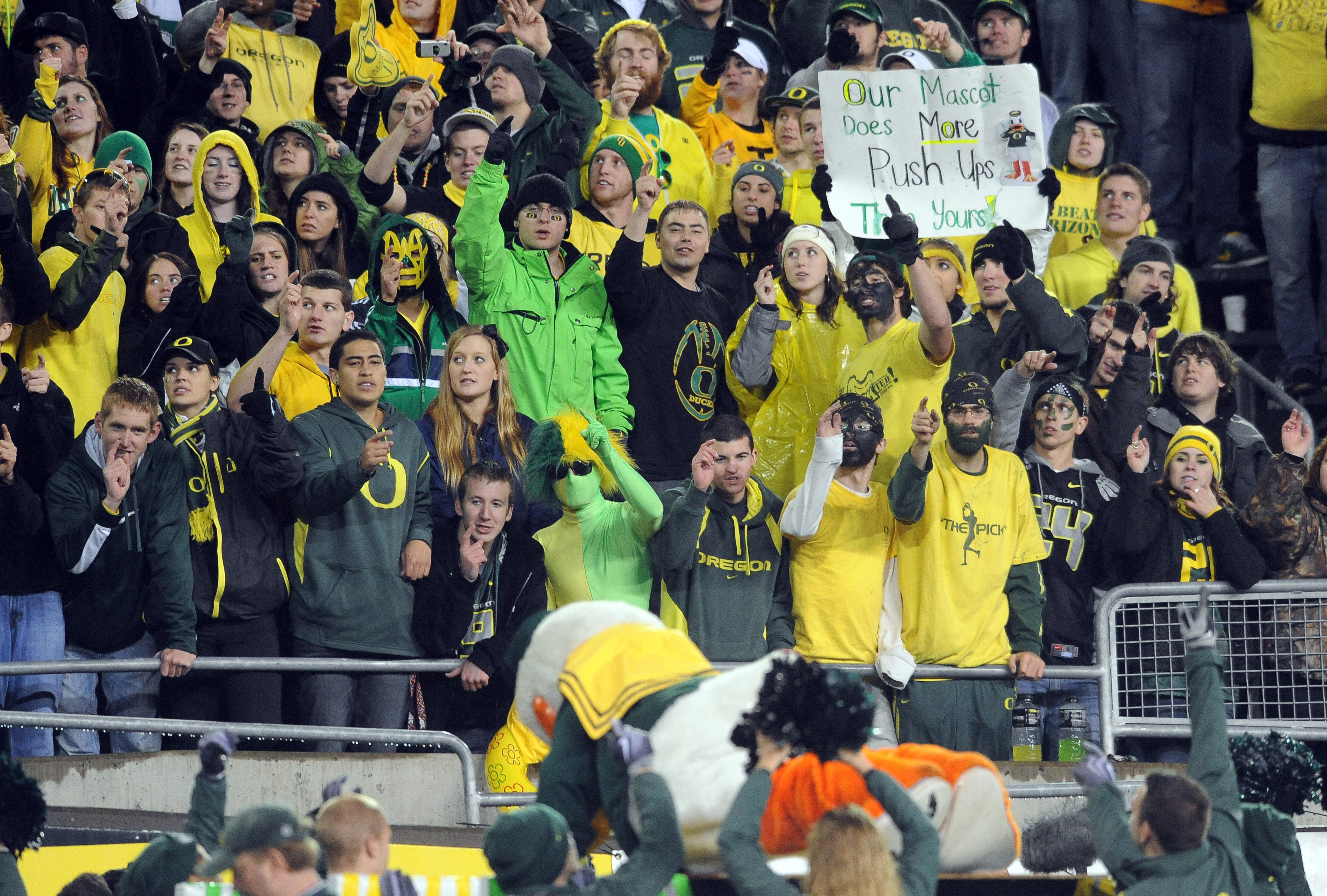 EUGENE, OR - NOVEMBER 26: Oregon Ducks fans cheer as mascot 'Puddles' does push ups in the fourth quarter of the game against the Arizona Wildcats at Autzen Stadium on November 26, 2010 in Eugene, Oregon. The Ducks won the game 48-29. (Photo by Steve Dyke
