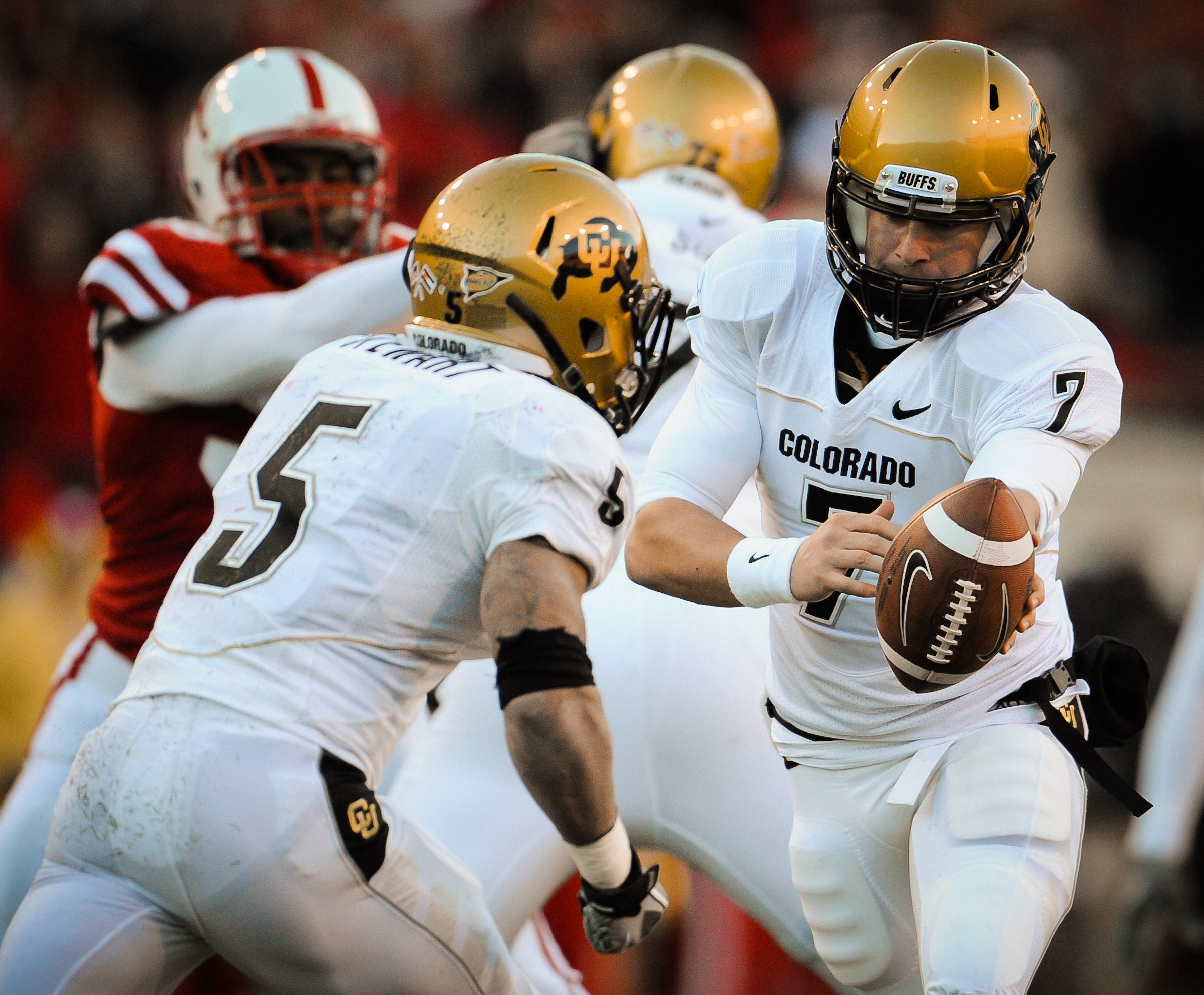 LINCOLN, NE - NOVEMBER 26: Cody Hawkins #7 hands the ball to teammate Rodney Stewart #5 of the Colorado Buffaloes during their game against the Colorado Buffaloes at Memorial Stadium on November 26, 2010 in Lincoln, Nebraska. Nebraska defeated Colorado 45