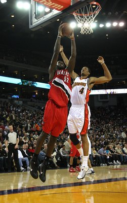 OAKLAND, CA - NOVEMBER 20:  Greg Oden #52 of the Portland Trail Blazers dunks over Anthony Randolph #4 of the Golden State Warriors during an NBA game at Oracle Arena on November 20, 2009 in Oakland, California.  (Photo by Jed Jacobsohn/Getty Images)