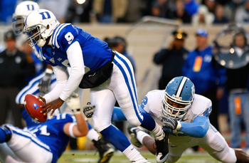 DURHAM, NC - NOVEMBER 29:  Quarterback Thaddeus Lewis #9 of the Duke Blue Devils is sacked by Robert Quinn #42 of the North Carolina Tar Heels during the game at Wallace Wade Stadium on November 29, 2008 in Durham, North Carolina.  (Photo by Kevin C. Cox/