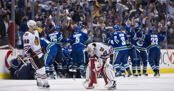 VANCOUVER, CANADA - APRIL 26: Troy Brouwer #22 of the Chicago Blackhawks skates towards goalie Corey Crawford #50 as the Vancouver Canucks celebrate after defeating the Blackhawks 2-1 in overtime of Game Seven of the Western Conference Quarterfinals durin