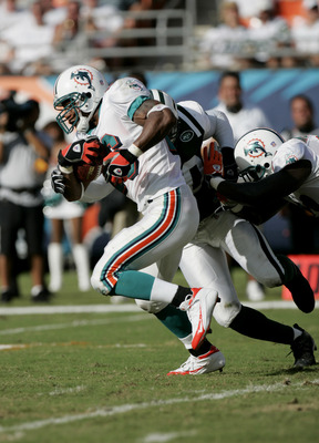 MIAMI - OCTOBER 3:  Runningback Leonard Henry #26 of the Miami Dolphins is nearly tackled by the New York Jets during the game at Pro Player Stadium on October  3, 2004 in Miami, Florida. The Jets won 17-9.  (Photo by Eliot J. Schechter/Getty Images)