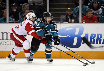 SAN JOSE, CA - NOVEMBER 30:  Niklas Kronwall #55 of the Detroit Red Wings and Logan Couture #39 of the San Jose Sharks go for the puck at HP Pavilion on November 30, 2010 in San Jose, California.  (Photo by Ezra Shaw/Getty Images)