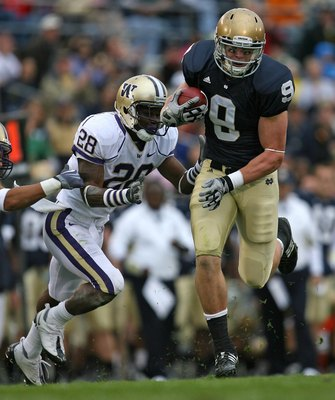 SOUTH BEND, IN - OCTOBER 03: Kyle Rudolph #9 of the Notre Dame Fighting Irish breaks away from Quinton Rochardson #28 of the Washington Huskies after catching the ball on October 3, 2009 at Notre Dame Stadium in South Bend, Indiana. Notre Dame defeated Wa
