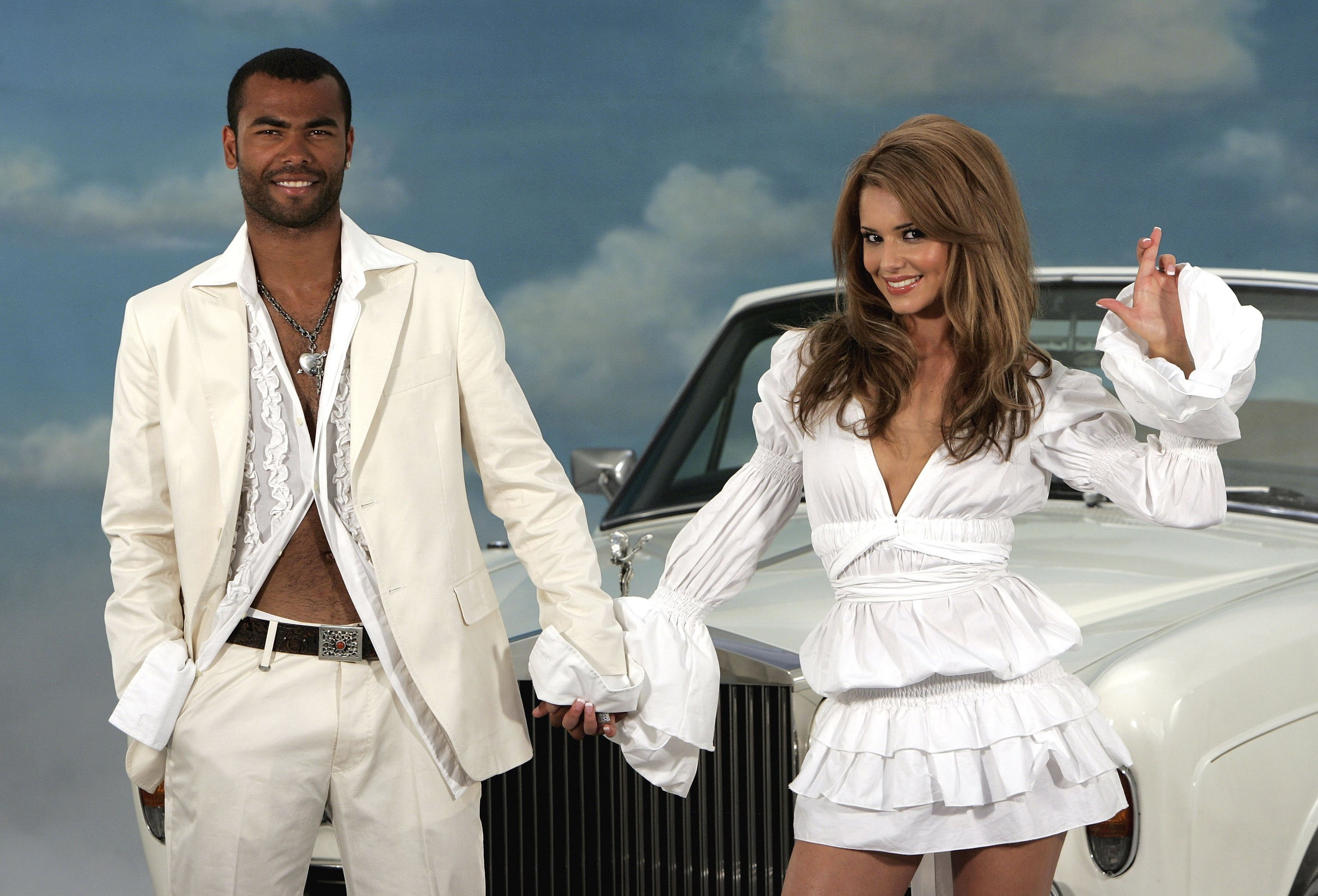 LONDON - JULY 11:  Singer Cheryl Tweedy of Girls Aloud and Footballer Ashley Cole pose in front of a Rolls Royce as they promote National Lottery's new Dream Number in Jasmine Studios on July 11, 2006 in London, England. Players can try to match all seven