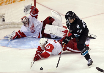 SAN JOSE, CA - APRIL 29:  Brad Stuart #23 and Jimmy Howard #35 of the Detroit Red Wings dive to stop a shot by Ryane Clowe #29 of the San Jose Sharks in Game One of the Western Conference Semifinals during the 2011 NHL Stanley Cup Playoffs at HP Pavilion