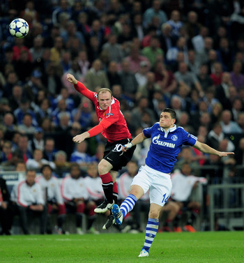 GELSENKIRCHEN, GERMANY - APRIL 26:  Kyriakos Papadopoulos of Schalke competes with Wayne Rooney of Manchester United during the UEFA Champions League Semi Final first leg match between FC Schalke 04 and Manchester United at Veltins Arena on April 26, 2011