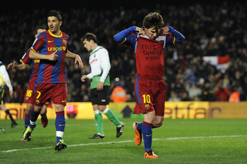 BARCELONA, SPAIN - JANUARY 22:  Lionel Messi of Barcelona (R) shows a shirt which it translates to 'Happy Birthday Mummy' as he celebrates after scoring his team's second goal during the La Liga match between Barcelona and Racing Santander at Camp Nou on