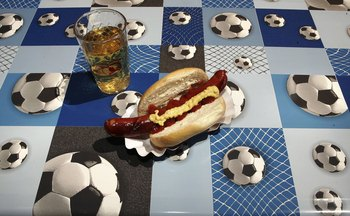 FRANKFURT, GERMANY - JUNE 11:  A hot dog and apple juice drink sit on a football patterned table cloth on June 11, 2006 in Frankfurt, Germany. On the third day of the FIFA World Cup three matches will take place in Leipzig, Nuremberg and Cologne.  (Photo