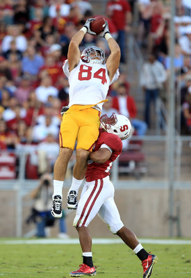 PALO ALTO, CA - OCTOBER 09:  Jordan Cameron #84 of the USC Trojans leaps to catch a ball over Delano Howell #26 of the Stanford Cardinal at Stanford Stadium on October 9, 2010 in Palo Alto, California. Cameron lost control of the ball on the way back down