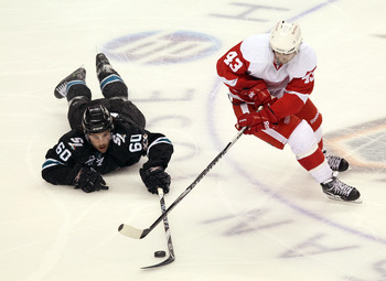 SAN JOSE, CA - APRIL 29:  Jason Demers #60 of the San Jose Sharks and Darren Helm #43 of the Detroit Red Wings go for the puck in Game One of the Western Conference Semifinals during the 2011 NHL Stanley Cup Playoffs at HP Pavilion on April 29, 2011 in Sa