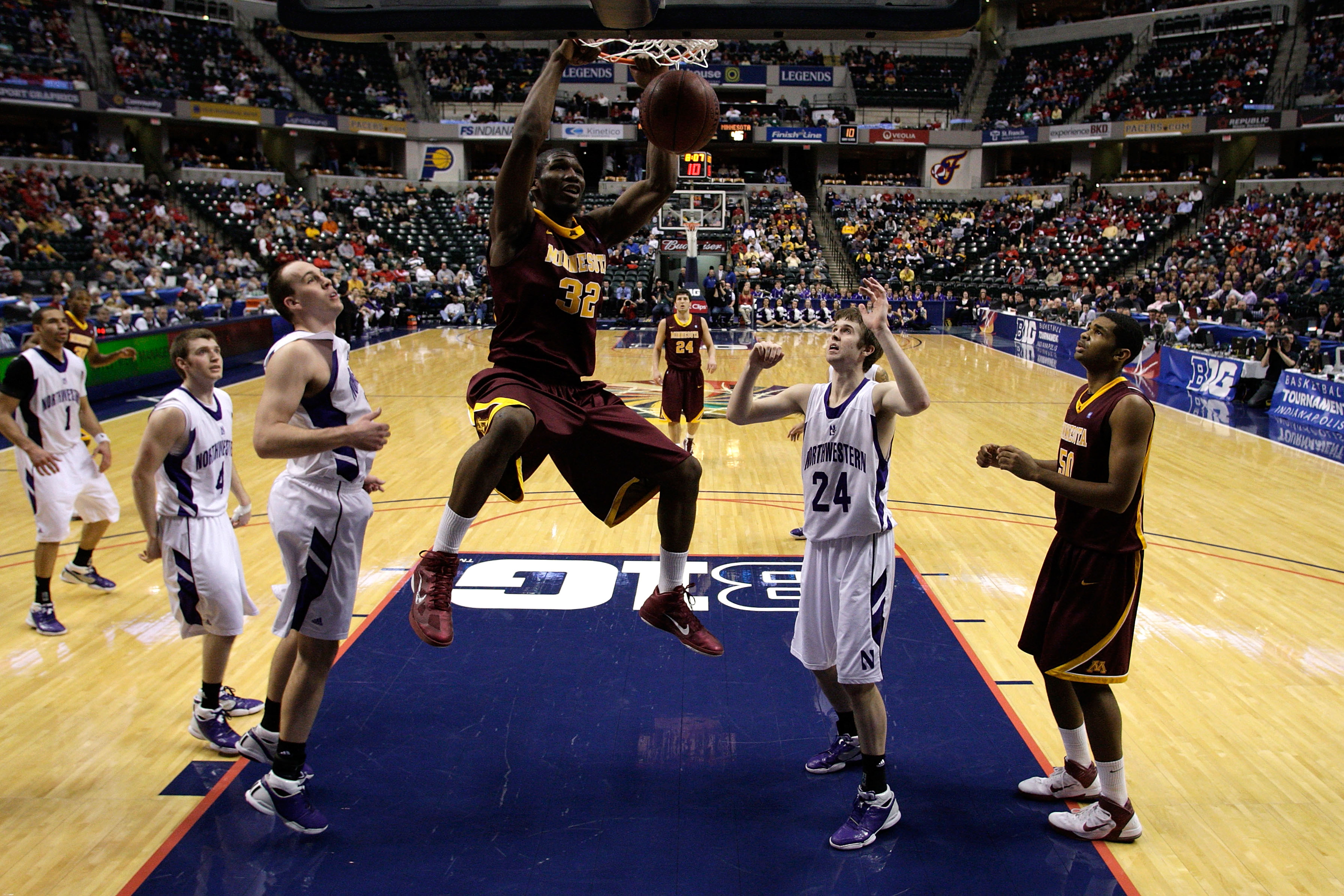 INDIANAPOLIS, IN - MARCH 10:  Trevor Mbakwe #32 of the Minnesota Golden Gophers dunks against John Shurna #24 of the Northwestern Wildcats during the first round of the 2011 Big Ten Men's Basketball Tournament at Conseco Fieldhouse on March 10, 2011 in In