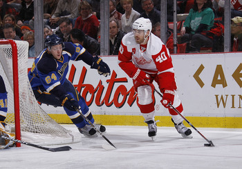 DETROIT, MI - MARCH 30:  Henrik Zetterberg #40 of the Detroit Red Wings skates with the puck along side Nikita Nikitin #64 of the St. Louis Blues at Joe Louis Arena on March 30, 2011 in Detroit, Michigan.  (Photo by Gregory Shamus/Getty Images)
