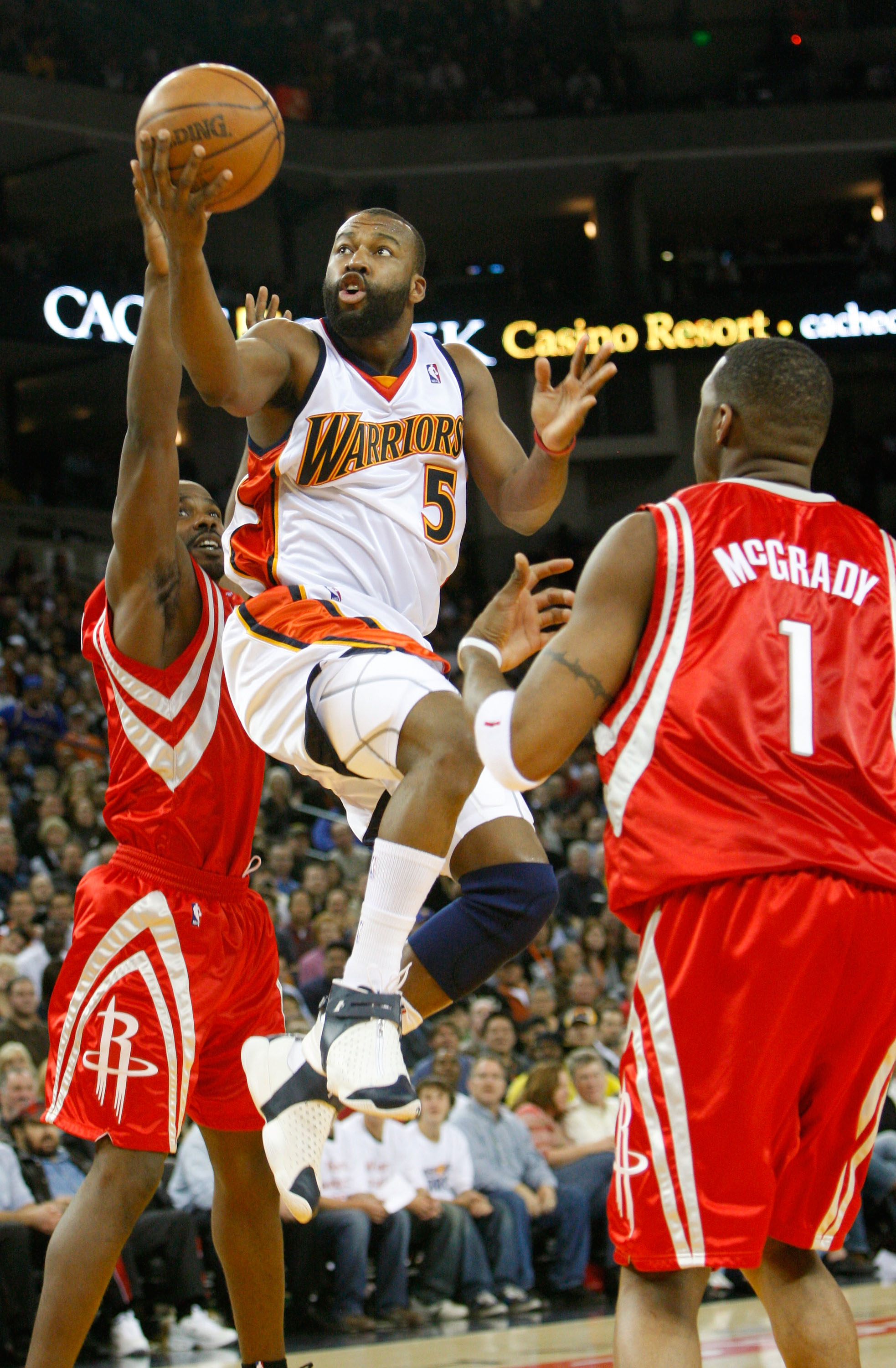 OAKLAND, CA - NOVEMBER 29:  Baron Davis #5 of the Golden State Warriors goes up for a shot as Tracy McGrady #1 of the Houston Rockets looks on during the second half November 29, 2007 at the Oracle Arena in Oakland, California. NOTE TO USER: User expressl