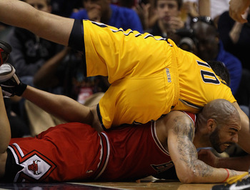 INDIANAPOLIS, IN - APRIL 23: Jeff Foster #10 of the Indiana Pacers lands on top of Carlos Boozer #5 of the Chicago Bulls during a scramble for a loose ball in Game Four of the Eastern Conference Quarterfinals in the 2011 NBA Playoffs at Conseco Fieldhouse