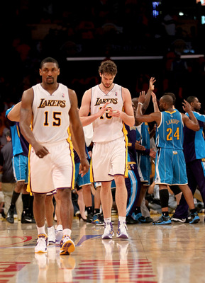 LOS ANGELES, CA - APRIL 17: Pau Gasol #16 and Ron Artest of the Los Angeles Lakers walk off the court as the New Orleans Hornets celebrate after Game One of the Western Conference Quarterfinals in the 2011 NBA Playoffs on April 17, 2011 at Staples Center