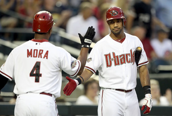 PHOENIX, AZ - APRIL 28:  Chris Young #24 of the Arizona Diamondbacks high fives teammate Melvin Mora #4 after scoring against the Chicago Cubs during the first inning of the Major League Baseball game at Chase Field on April 28, 2011 in Phoenix, Arizona.