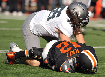 CORVALLIS, OR - DECEMBER 4: Quarterback Ryan Katz #12 of the Oregon State Beavers lays on the turf after being hit by Casey Matthews #55 of the Oregon Ducks in the first quarter of the game at Reser Stadium on December 4, 2010 in Corvallis, Oregon. The Du