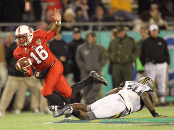 ORLANDO, FL - DECEMBER 28:  Russell Wilson #16 of the North Carolina State Wolfpack scrambles to get away from J.T. Thomas #30 of the West Virginia Mountineers during the Champs Sports Bowl at Florida Citrus Bowl Stadium on December 28, 2010 in Orlando, F