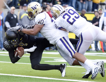 EUGENE, OR - NOVEMBER 06: Linebacker Mason Foster #40 safety Nate Fellner #29 of the Washington Huskies tackle quarterback Darron Thomas #1 of the Oregon Ducks as Thomas crosses the goal line for a touchdown in the third quarter of the game at Autzen Stad