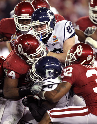 GLENDALE, AZ - JANUARY 01:  Jordan Todman #23 of the Connecticut Huskies is tackled by Jeremy Beal #44 and Jamell Fleming #32 of the Oklahoma Sooners in the first half during the Tostitos Fiesta Bowl at the Universtity of Phoenix Stadium on January 1, 201