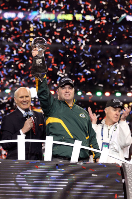 ARLINGTON, TX - FEBRUARY 06:  Head coach Mike McCarthy of the Green Bay Packers celebrates with the Vince Lombardi trophy as FOX analyast Terry Bradshaw and Packers' General manager Ted Thompson looks on following the Packers 31-25 win in Super Bowl XLV a