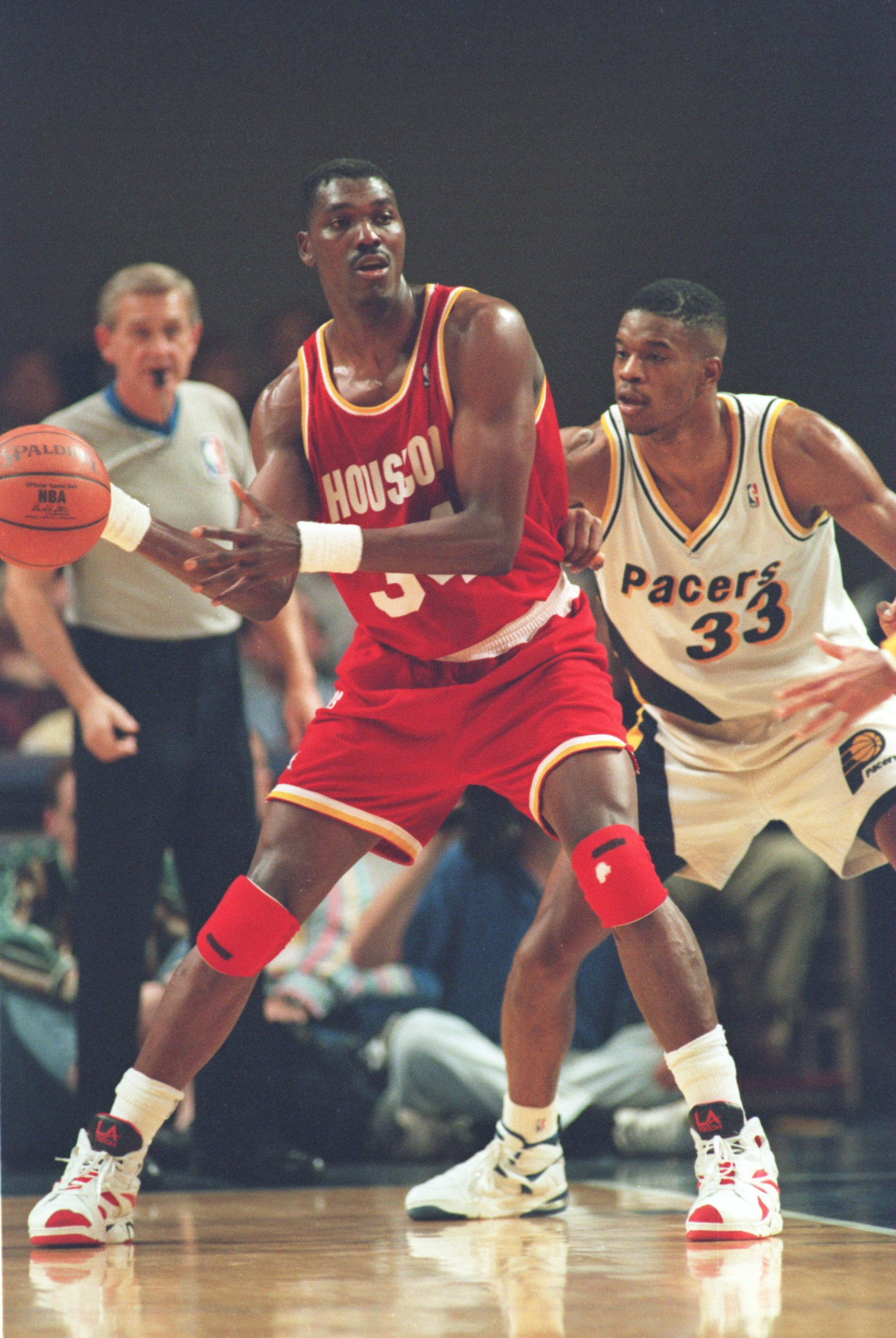 INDIANAPOLIS - NOVEMBER 9: Center Hakeem Olajuwon #34 of the Houston Rockets backs into Antonio Davis #33 of the Indiana Pacers in an attempt to gain post position during their game on November 9, 1994 at Market Square Arena in Indianapolis, Indiana. The