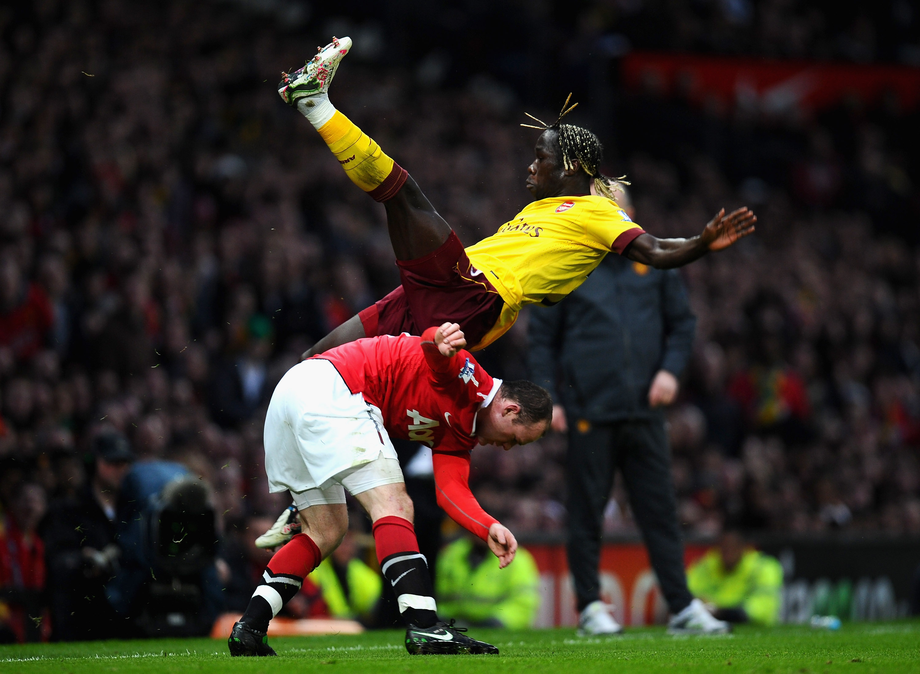 MANCHESTER, ENGLAND - MARCH 12:  Bacary Sagna of Arsenal falls over Wayne Rooney of Manchester United during the FA Cup sponsored by E.On Sixth Round match between Manchester United and Arsenal at Old Trafford on March 12, 2011 in Manchester, England.  (P