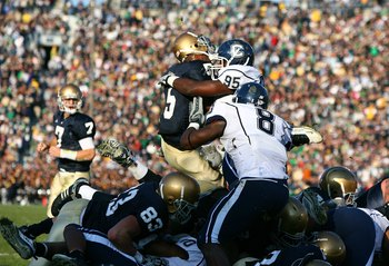 SOUTH BEND, IN - NOVEMBER 21: Armando Allen #5 of the Notre Dame Fighting Irish loses his helmet as he is hit at the goal line by Greg Lloyd #95 of the Univeristy of Connecticut Huskies at Notre Dame Stadium on November 21, 2009 in South Bend, Indiana. (P