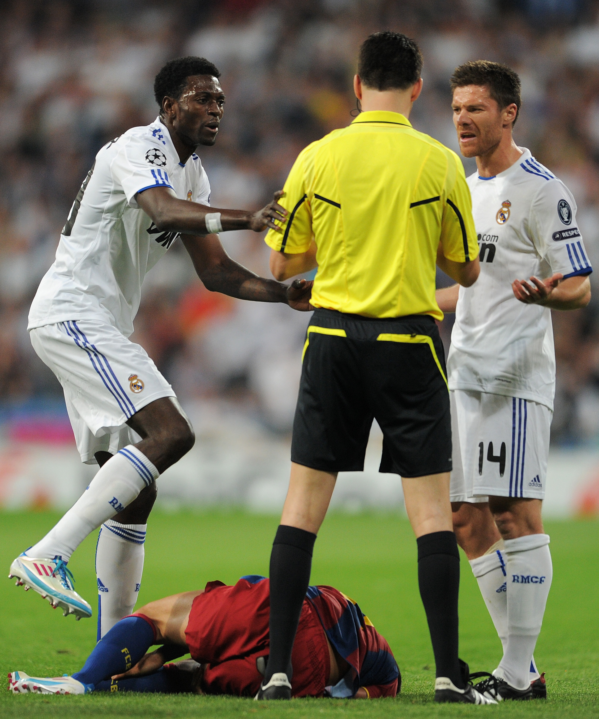 MADRID, SPAIN - APRIL 27:  Emmanuel Adebayor (L) and Xabi Alonso (R) of Real Madrid argue with referee Wolfgang Stark (C) as Daniel Alves of Barcelona lays on the pitch after being fouled by Pepe during the UEFA Champions League Semi Final first leg match
