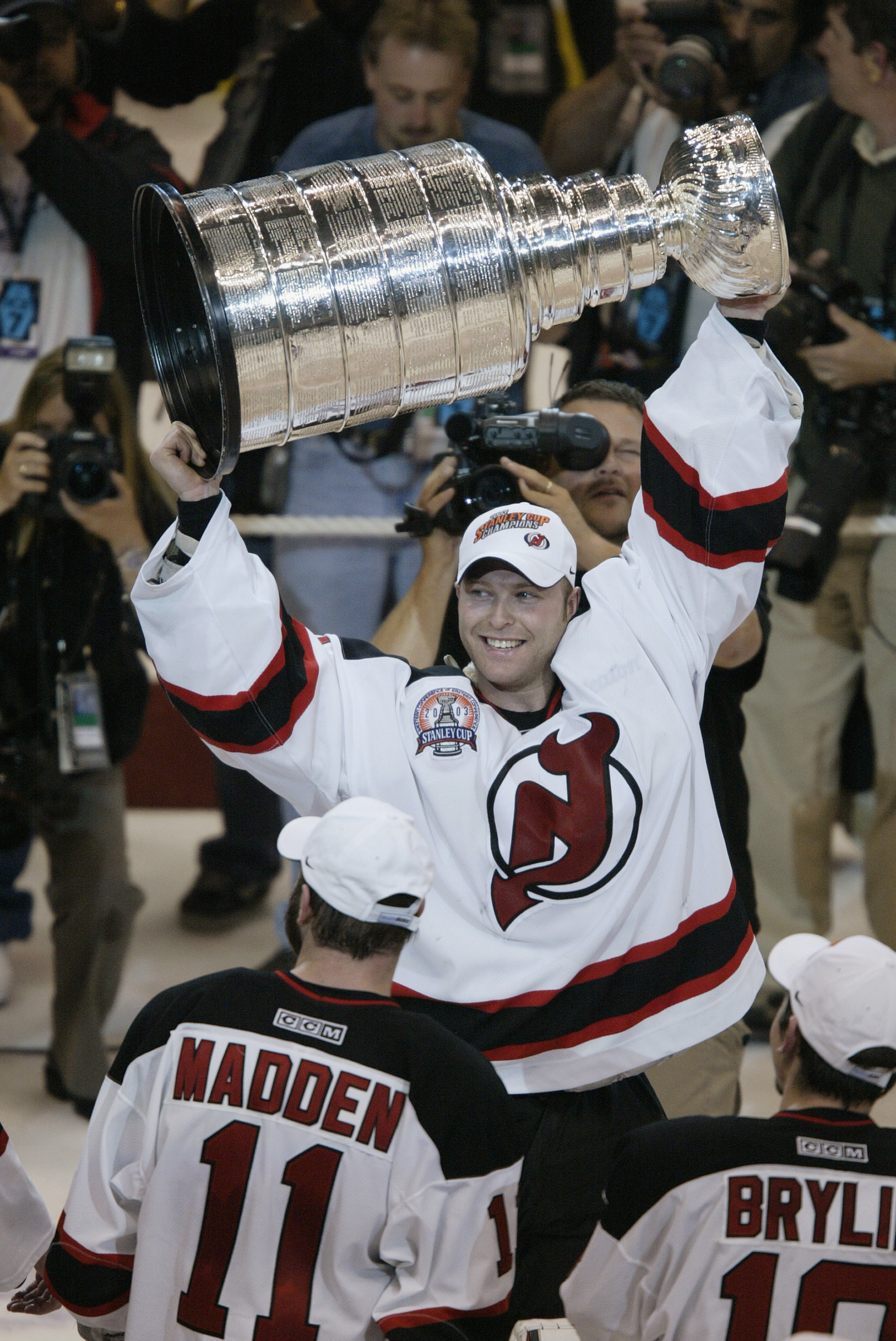 EAST RUTHERFORD, NJ - JUNE 9:  Goalie Martin Brodeur #30 holds up the Stanley Cup trophy after defeating the Mighty Ducks of Anaheim 3-0 in game seven of the 2003 Stanley Cup Finals at Continental Airlines Arena on June 9, 2003 in East Rutherford, New Jer
