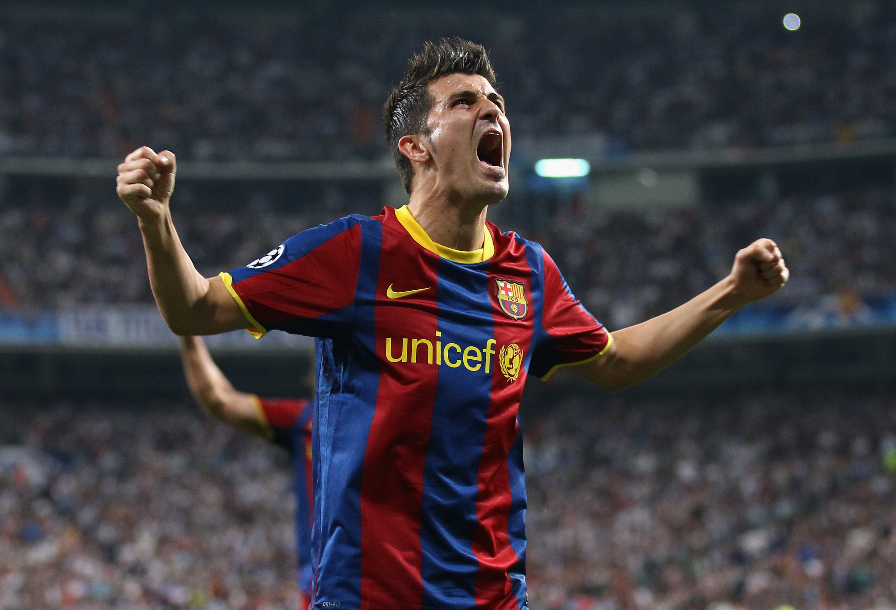MADRID, SPAIN - APRIL 27:  David Villa of Barcelona celebrates after Lionel Messi scores the opening goal during the UEFA Champions League Semi Final first leg match between Real Madrid and Barcelona at Estadio Santiago Bernabeu on April 27, 2011 in Madri