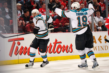 DETROIT - MAY 4:  Devin Setoguchi #16 of the San Jose Sharks celebrates his first period power play goal against the Detroit Red Wings with teammate Joe Thornton #19 of the San Jose Sharks in Game Three of the Western Conference Semifinals during the 2011