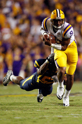 BATON ROUGE, LA - SEPTEMBER 25:  Jordan Jefferson #9 of the Louisiana State Univeristy Tigers avoids a tackle by Najee Goode #52 of the West Virginia Mountaineers at Tiger Stadium on September 25, 2010 in Baton Rouge, Louisiana.  (Photo by Chris Graythen/