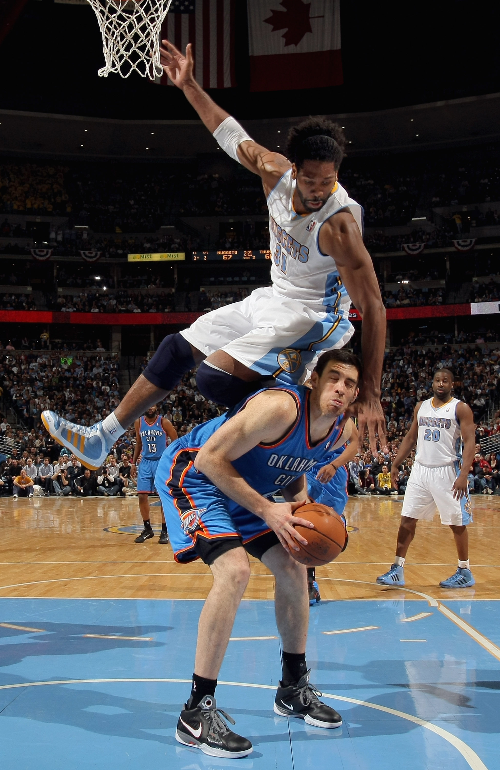 DENVER, CO - APRIL 25:  Nick Collison #4 of the Oklahoma City Thunder tries to get off a shot but is fouled by Nene Hilario #31 of the Denver Nuggets in Game Four of the Western Conference Quarterfinals in the 2011 NBA Playoffs on April 24, 2011 at the Pe