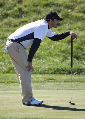 PEBBLE BEACH, CA - FEBRUARY 11:  Professional football player Tony Romo lines up a putt at the AT&T Pebble Beach National Pro-Am- Round Two at the Spyglass golf club on February 11, 2011 in Pebble Beach, California.  (Photo by Jed Jacobsohn/Getty Images)