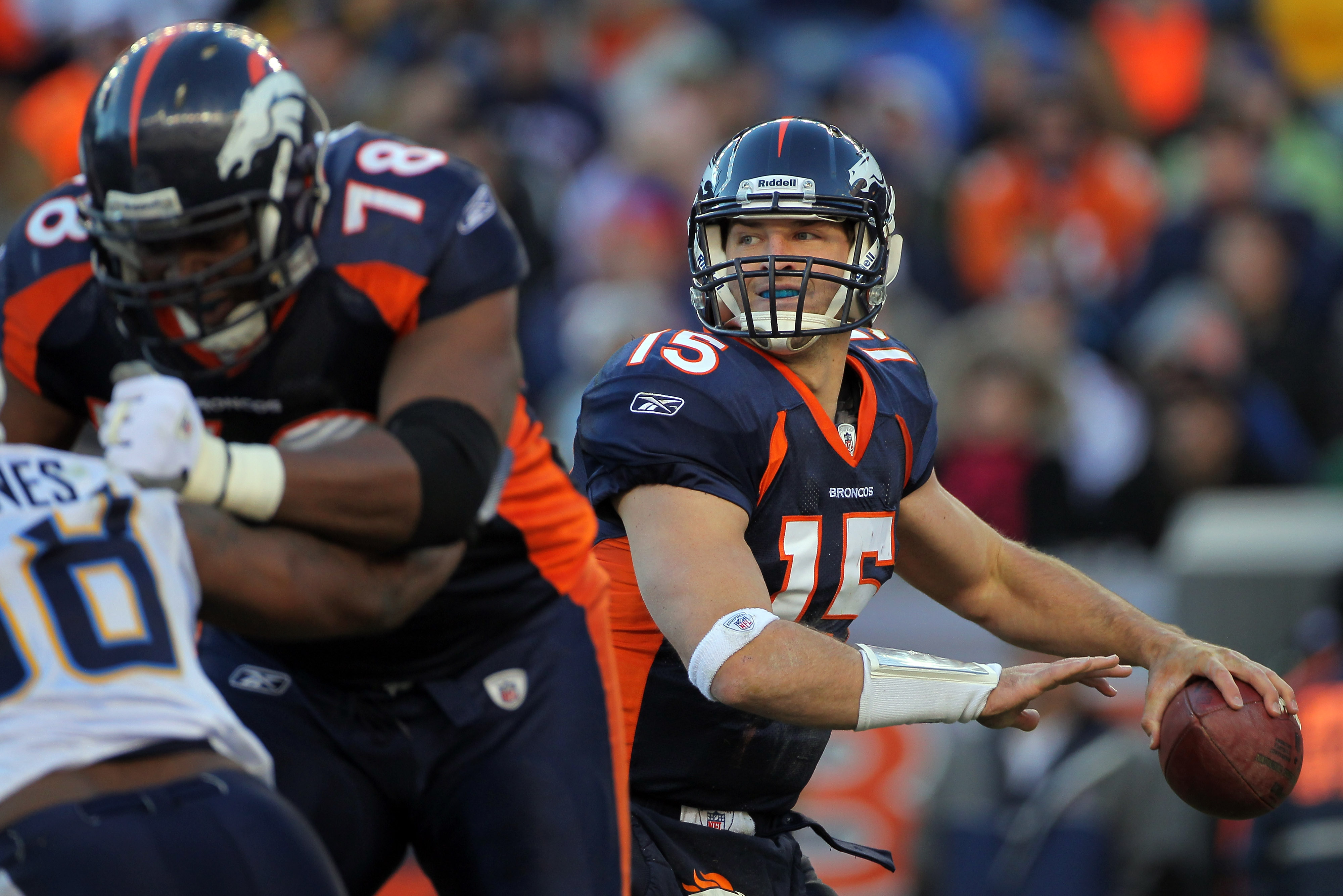 DENVER - JANUARY 02:  Quarterback Tim Tebow #15 of the Denver Broncos looks to deliver a pass behind the protection of offensive lineman Ryan Clady #78 as he blocks Antwan Barnes #98 of the San Diego Chargers at INVESCO Field at Mile High on January 2, 20