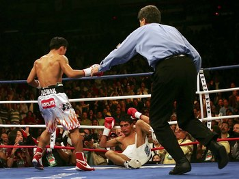 LAS VEGAS - NOVEMBER 18:  (L-R) Manny Pacquiao of the Philippines looks down as Erik Morales of Mexico is knocked down for the second time in round three during their super featherweight bout at the Thomas & Mack Center on November 18, 2006 in Las Vegas,