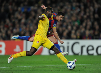 BARCELONA, SPAIN - MARCH 08:  David Villa (R) of Barcelona shoots on goal past Johan Djourou of Arsenal during the UEFA Champions League round of 16 second leg match between Barcelona and Arsenal on March 8, 2011 in Barcelona, Spain.  (Photo by Jasper Jui