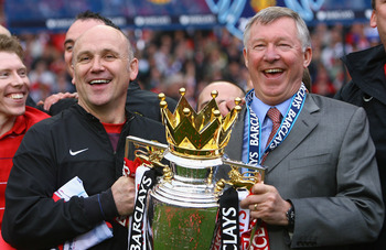 MANCHESTER, ENGLAND - MAY 16:  Manchester United Manager Sir Alex Ferguson (R) and Assistant Mike Phelan celebrate with the Barclays Premier League trophy after their side won the Premier League title at the end of the Barclays Premier League match betwee